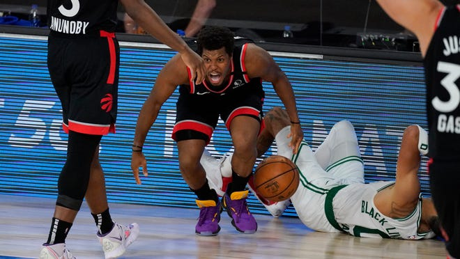 Toronto Raptors' Kyle Lowry (7) celebrates in front of Boston Celtics' Jayson Tatum (0) during the second half of an NBA conference semifinal playoff basketball game Saturday, Sept. 5, 2020, in Lake Buena Vista, Fla.