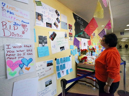 Susan Cordova, Educational Diagnostician at Canutillo Middle School reads some of the many messages left on a memorial to 8th grade student Diego Fernandez, 14, Friday at the school's entrance. Fernandez, 14, an advanced placement student and soccer team member died in a traffic accident Thursday night.