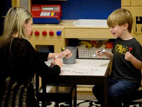 Whitehall Pre-K teacher Jennifer Horner draws on a whiteboard table with her student, Brody Parnell, in this 2017 file photo, during an open house for the school's temporary location at Nova.