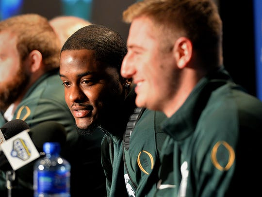 Quarterback Connor Cook smiles as receiver Aaron Burbridge