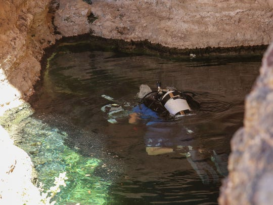 Biologist Jeff Goldstein with the National Park Service uses an underwater stereoscopic camera to record the size of Desert Pupfish at the Devil's Hole geothermal