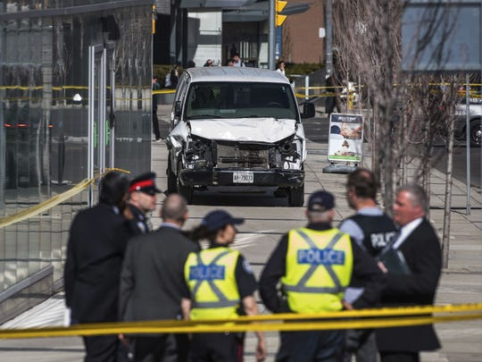 Police are seen near a damaged van after a van mounted a sidewalk colliding with pedestrians in Toronto on April 23, 2018.