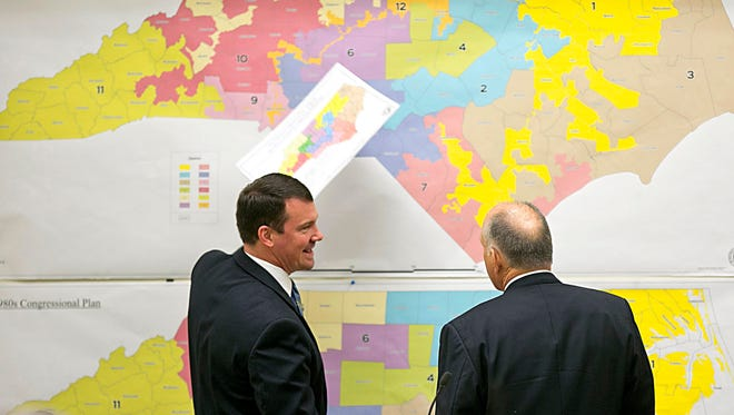 FILE - In this Tuesday, Feb. 16, 2016 file photo, Republican state Sens. Dan Soucek, left, and Brent Jackson, right, review historical maps during The Senate Redistricting Committee for the 2016 Extra Session in the Legislative Office Building at the N.C. General Assembly, in Raleigh, N.C. An Associated Press analysis, using a new statistical method of calculating partisan advantage, finds traditional battlegrounds such as Michigan, North Carolina, Pennsylvania, Wisconsin, Florida and Virginia were among those with significant Republican advantages in their U.S. or state House races in 2016.