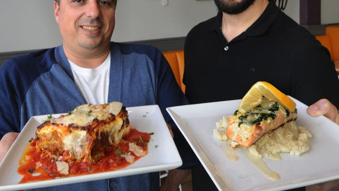 Joby Yobe, left, displays Loaded Lasagna and Jorge Alem, holds C-Street Salmon, at the newly opened The 2686 Kitchen in Ventura. The pair co-own the restaurant.