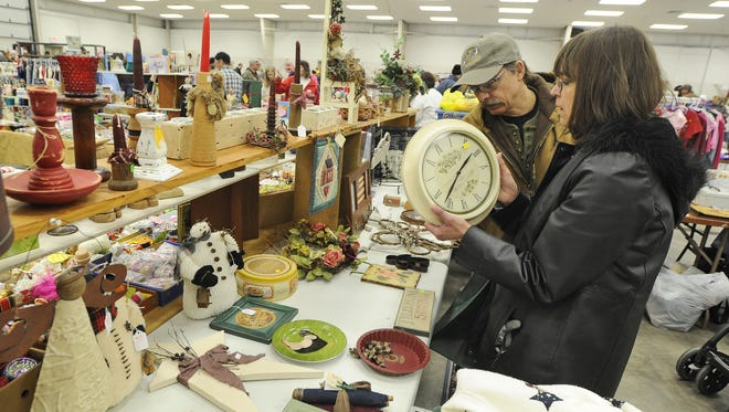 Jerry and Kathy Zychowski of Menomonee Falls look at a wall clock at one of the booths in the Action Reporter Media Ultimate Indoor Garage Sale at the Fond du Lac County Fairgrounds in 2013.