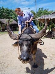 Kyla Mora, Pacific Daily News reporter, rides a carabao