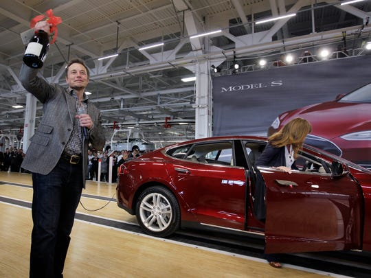 In this June 22, 2012 file photo, Tesla Motors CEO Elon Musk holds up a bottle of wine given as a gift from one of their first customers at Tesla's plant in Fremont, Calif.