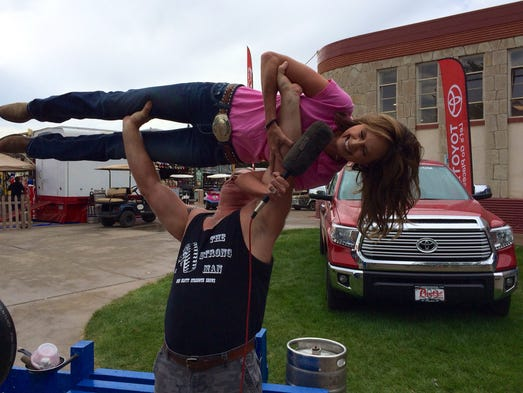 Strongman John Beatty lifts KUSA-TV meteorologist Kathy Sabine aloft during a demonstration at the Colorado State Fair.