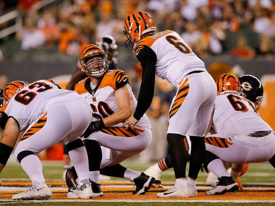 Cincinnati Bengals center T.J. Johnson (60) turns back to quarterback Jeff Driskel (6) for clarification before a snap in the fourth quarter of the NFL Preseason Game One between the Cincinnati Bengals and the Chicago Bears at Paul Brown Stadium in downtown Cincinnati on Thursday, Aug. 9, 2018. The Bengals won the pre-season opener, 30-27.