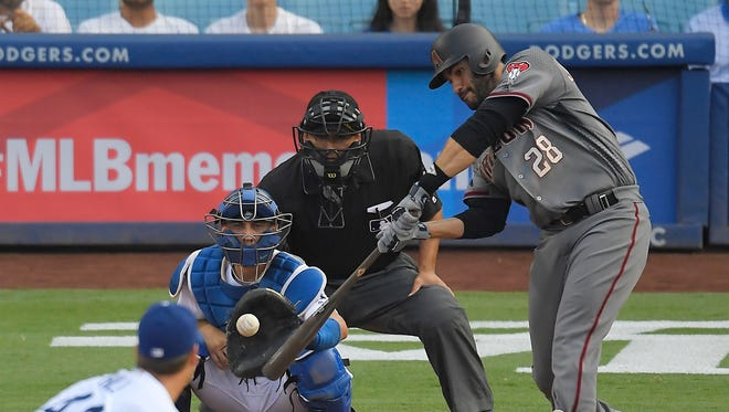 Arizona Diamondbacks' J.D. Martinez, right, hits a two-run home run as Los Angeles Dodgers starting pitcher Rich Hill, left, watches along with catcher Austin Barnes, second from left, and home plate umpire Alfonso Marquez during the fourth inning of a baseball game, Monday, Sept. 4, 2017, in Los Angeles. (AP Photo/Mark J. Terrill)