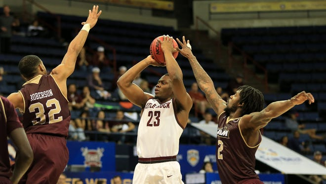 Justin Roberson (32) and DeMondre Harvey (2) contest a Kemy Osse (23) jumper during ULM's 70-50 loss to Little Rock in the Sun Belt tournament finals.