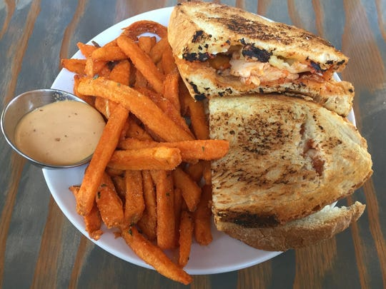 A beer can chicken sandwich at Midtown Eats is built with barbecue sauce and melty smoked Gouda. Sweet potato fries ride sidecar.
