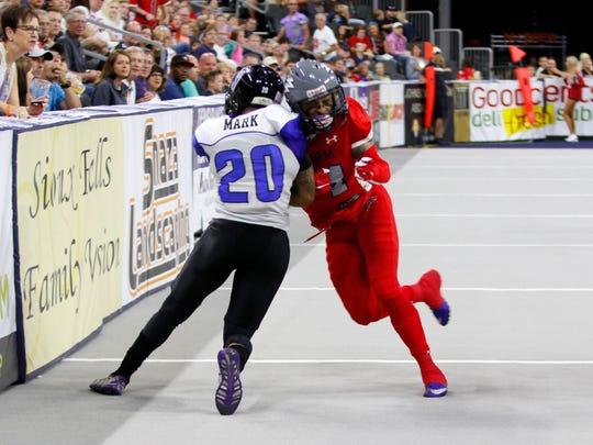 Sioux Falls Storm receiver Brandon Johnson-Farrell absorbs a blow from the Cedar Rapids Titans' Venric Mark.
