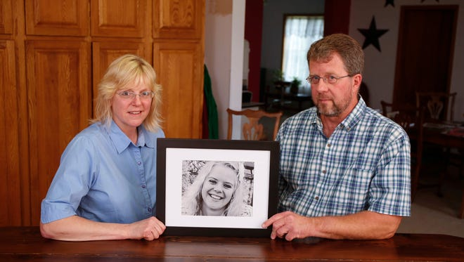 Darrel and Christine Harken of Riceville hold a photo of their daughter Grace, who was killed when her bicycle was struck by a driver who was texting on a road near Osage last July.
