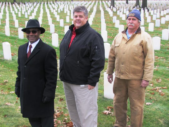 Standing at Woodlawn National Cemetery in Elmira are,