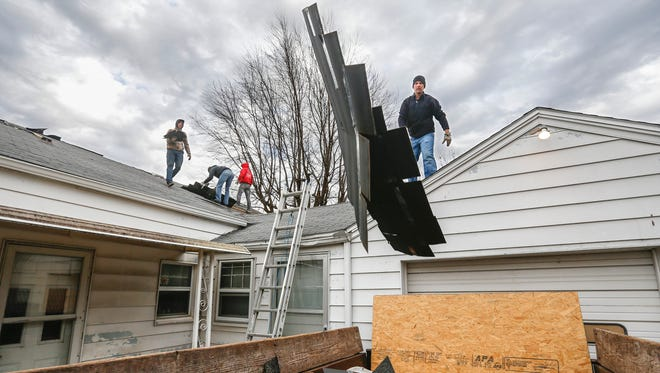 Kevin Hanson, of Hanson Roofing & Exteriors, tosses shingles into a dumpster while working on a roof on Tuesday, January 24, 2017. A proposed bill would create a registration process for roofers.