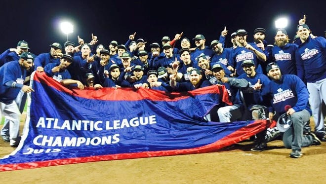 The 2015 champion Somerset Patriots pose with the banner they won Monday night by defeating the Southern Maryland Blue Crabs.