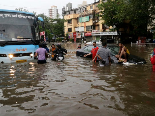 Commuters make their way through a flooded street following
