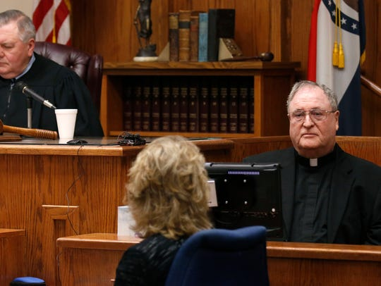 Father Mike McDevitt testifies in court during the