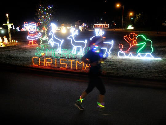 A runner passes by a display during the Christmas Lane 5K on Thursday, Dec. 1, 2016, at the Abilene State Supported Living Center.