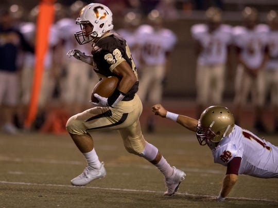 Central's Reeder Pennell (22) eludes the tackle of Mater Dei's Luke Kassenbrock (17) at Central Stadium Friday night.