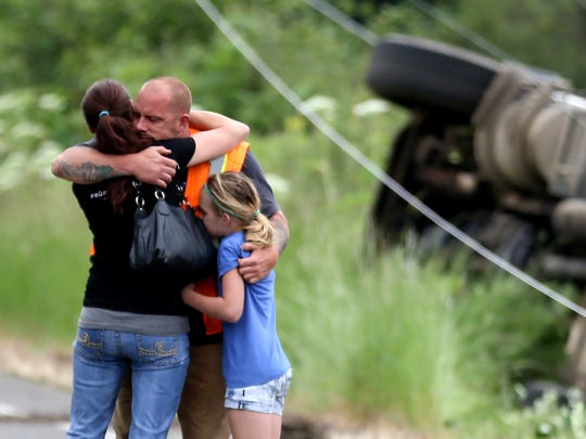Chris Nonamaker hugs his wife and daughter after the cement truck he was driving rolled over on River Road S in Salem on Friday, May 20, 2016. The truck knocked down two power poles causing outages for nearby residents.