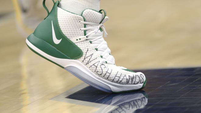"""Boston Celtics center Enes Kanter wears shoes with """"wash hands"""" written on them during the second half of the team's NBA game against the Indiana Pacers in Indianapolis on March 10, 2020. The Celtics will meet in Florida later this week to resume the NBA season."""