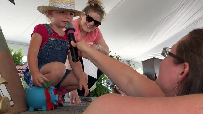 Kayla Christiansen, left, of Port Clinton, competes in the hog calling contest with coaching from her mom, Brittany, at the 2015 Ottawa County Fair.