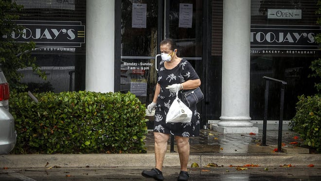 A woman exits Toojay's in Palm Beach Thursday with a pickup order. The company has filed for bankruptcy, citing the fallout from the coronavirus.