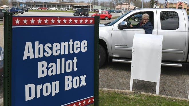 A voter drops off her absentee ballot in the dropbox of the Stark County Board of Elections in Canton on April 24 during primary voting.