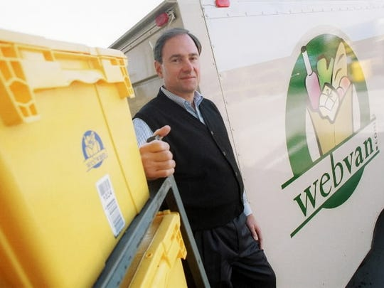 George Shaheen, CEO of since bankrupt Webvan, is shown outside the company's 330,000 square foot Oakland distribution center next to a company van and totes which hold the groceries in June 2000.