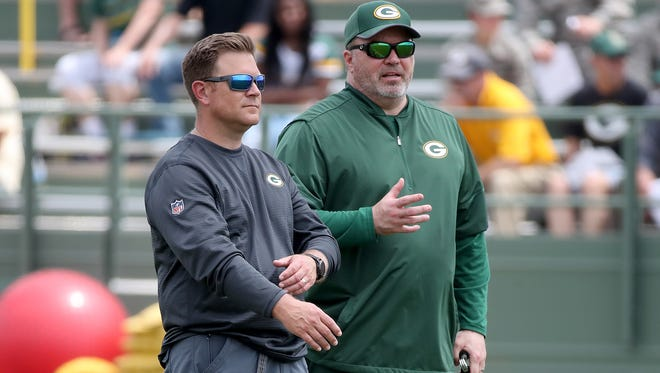 Green Bay Packers coach Mike McCarthy, right, talks with general manager Brian Gutekunst during minicamp on June 12, 2018, at Ray Nitschke Field.