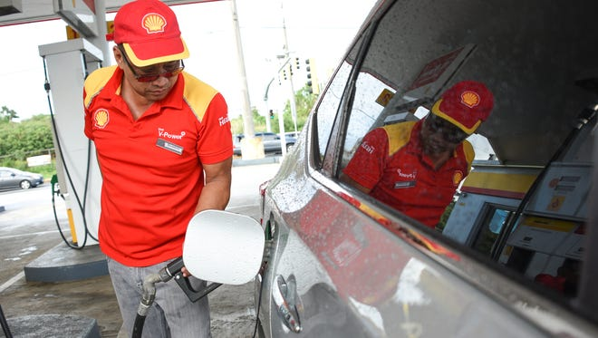 In this file photo, customer service attendant Dominic Jose replenishes the fuel in a motorist's vehicle at the Tiyan Shell gas station.