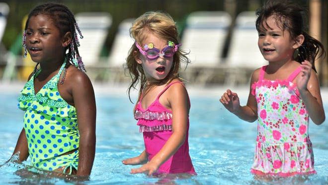 Ready to swim, (from left) London Turner, 6, Adrianna Deroso, 6, and Giselle Zamora, 6, all from the Fort Pierce Police Athletic League Summer Camp, prepared to take part in the World's Largest Swimming Lesson Event June 22, 2017, at the Lakewood Park Pool in northern St. Lucie County.