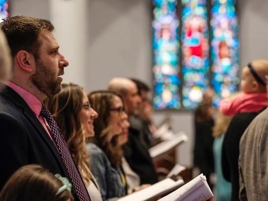 Members of St. Paul's Episcopal Church in Lansing sing during services on Easter Sunday, April 1, 2018. The church has been undergoing repairs since last year. Sunday was the first day back in the original worship space since the front wall of the building nearly collapsed during a wind storm in March 2017.