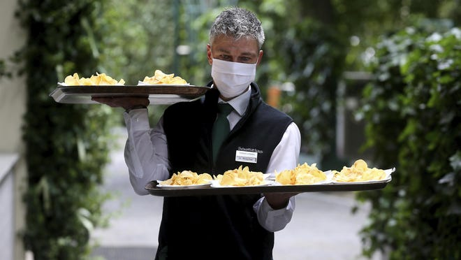 A waiter with a face mask carries food in a restaurant in Vienna, Austria, Thursday, May 14.