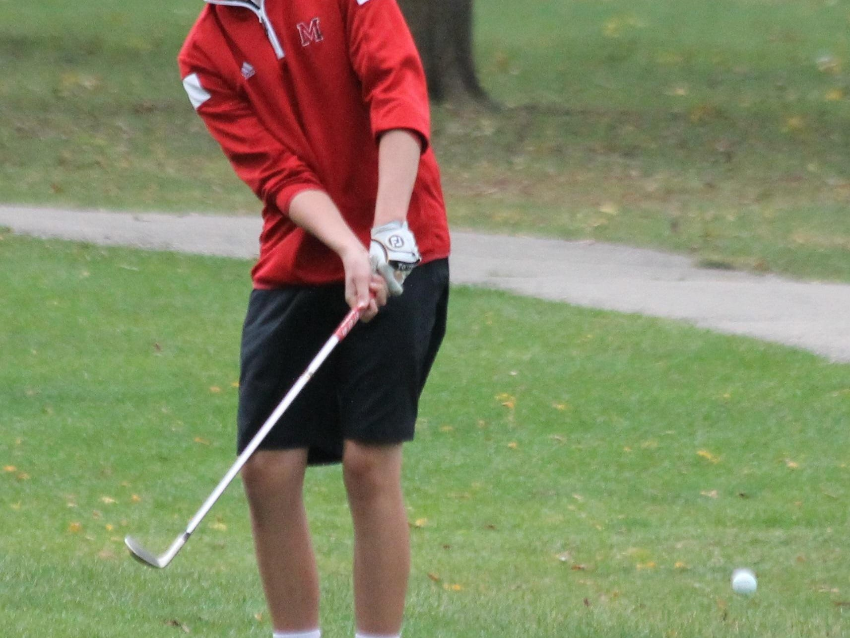Junior Nathan Arnold watches his chip shot. He finished the round with a 76.