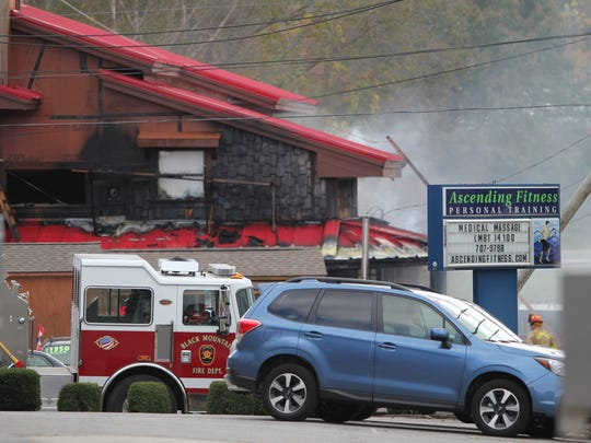 An engine from the Black Mountain Fire Department sits in front of the north side of Black Mountain Stove & Chimney as firefighters extinguish flames inside.