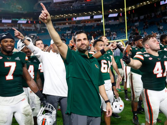 Miami coach Manny Diaz, center, celebrates with players after Miami defeated Louisville 52-27 during an NCAA college football game Saturday, Nov. 9, 2019, in Miami Gardens, Fla. (AP Photo/Wilfredo Lee)