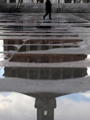 A pedestrian makes her way across a wet War Memorial Plaza as the the State Capitol reflects in rain puddles after a rainstorm blew through Thursday, March 31, 2016, in Nashville, Tenn.