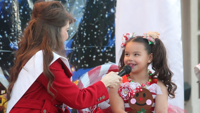Raquel Holmes, 7 years old, answers questions during the first Little Miss Christmas Pageant on Saturday.