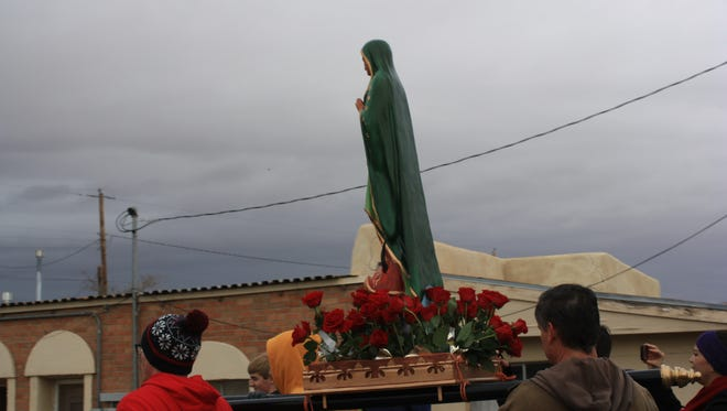 A Virgen de Guadalupe statue is carried by volunteers during a procession celebrating her feast day Saturday.