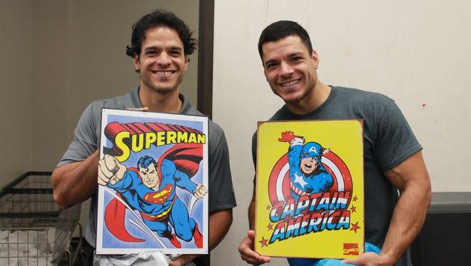 Mike and Matt Villanueva pose while holding metal poster of their favorite superheros.