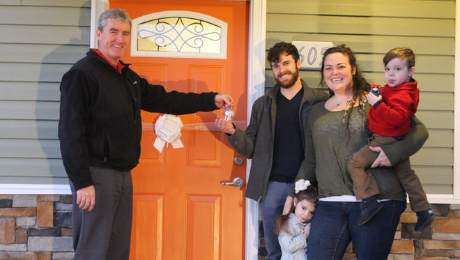 Zach and Nikki Newbold and kids receive the keys to their new home from Jeff Younginer, director of Product Quality at Nissan's Smyrna vehicle assembly plant.