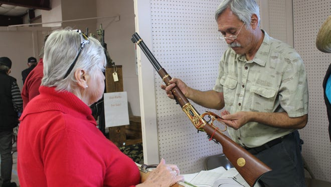 Eli Calles, Western Frontier Gun Shows organizer, helps appraise a gun that a woman inherited.
