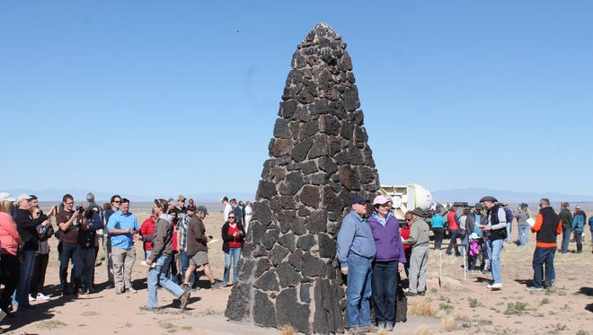 A couple stands in front of the Trinity Site obelisk that was declared a landmark in 1975.