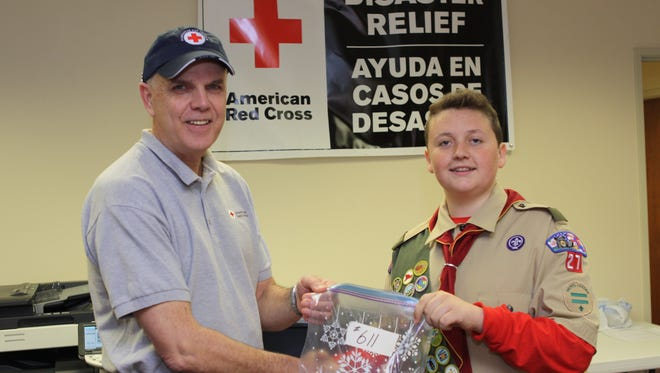 Richard Branigan with the American Red Cross accepts donations from Boy Scout Cutter Lawson. Lawson's efforts will help 600 flood victims.
