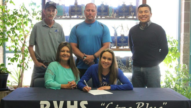 Beside her mother, and in front of track and field coaches Mark Turner, top left, and Jared Howell, and cross-country coach Sampson Sage, Piedra Vista's Cassandra Crowell poses for a photo on Wednesday at Piedra Vista High School after signing her national letter of intent to run at the Lubbock Christian University in Lubbock, Texas.