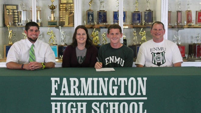 Surrounded by his parents and high school head coach Byron Farnsworth, left, Farmington's Peyton Rasmussen signs his commitment Wednesday at Farmington High School to play soccer at the University of Eastern New Mexico.