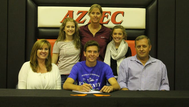Surrounded by family members and Aztec track and field coach Anna Strauss, top, Aztec's Lindsey Larabee signs his national letter of intent on Friday at Aztec High School to pole vault for the University of Nebraska-Kearney.